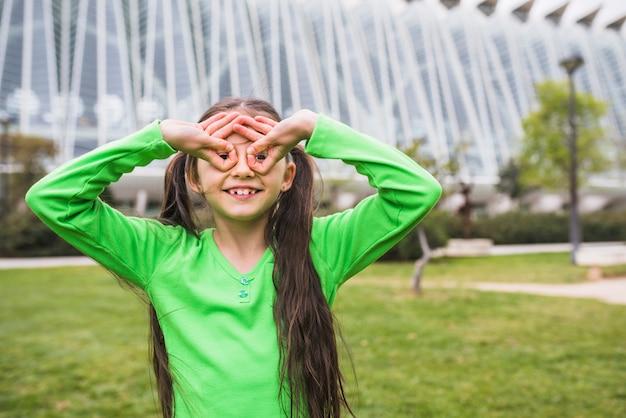 Garota feliz, formando óculos com o dedo em pé no parque Foto gratuita
