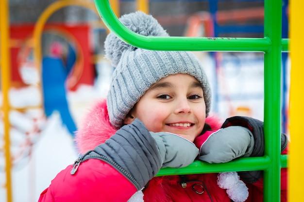 Garota feliz jogando em um playground no dia gelado de inverno. Foto Premium