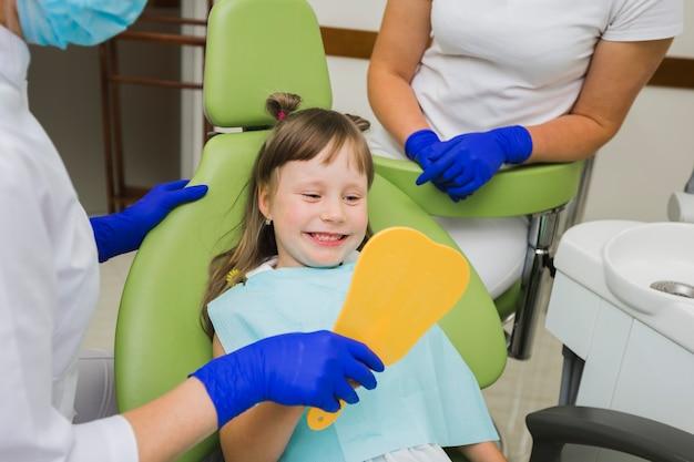 Garota feliz no dentista olhando no espelho Foto Premium