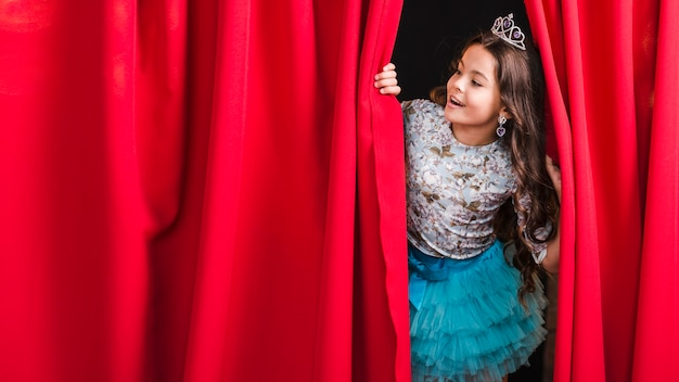 Garota feliz olhando através da cortina vermelha no palco Foto gratuita