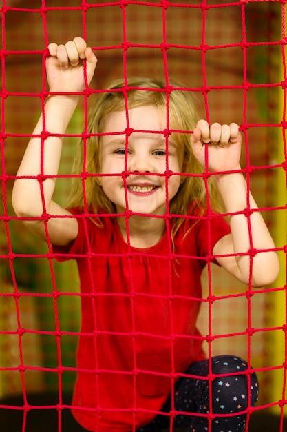 Garota feliz posando atrás da rede Foto gratuita