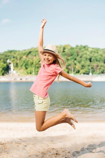 Garota feliz pulando na areia Foto gratuita