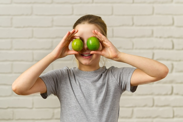 Garota feliz se divertindo e cobrindo os olhos com limão, alimentação saudável, alimentos orgânicos, dieta de frutas, conceito Foto Premium