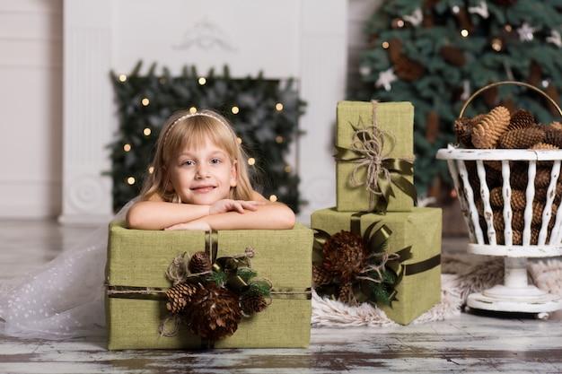 Garota feliz, segurando uma caixa grande com um presente na cabeça dela. conceito de férias de inverno, natal e pessoas. Foto Premium