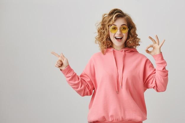 Garota feliz surpresa apontando para a esquerda, recomendar anúncio de produto, fazer gesto de aprovação Foto gratuita