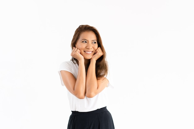 Garota feliz tocando as bochechas e estudando o espaço da cópia Foto gratuita
