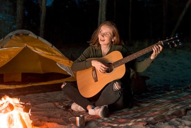 Garota feliz tocando guitarra por uma fogueira Foto gratuita