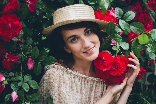 Garota fica contra uma parede de arbustos com rosas vermelhas Foto Premium