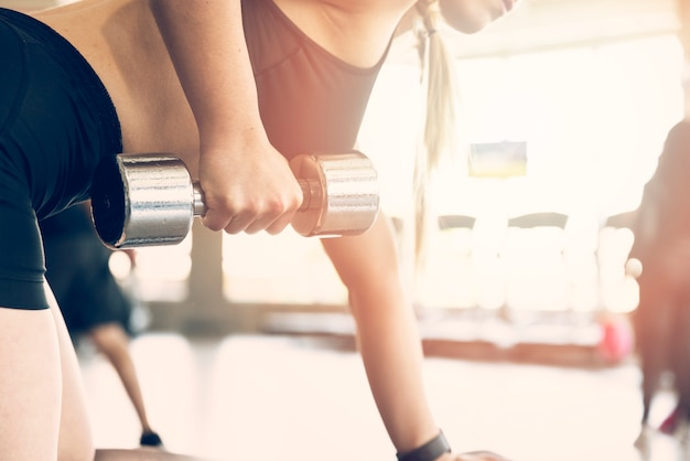 Garota fitness usando dumbball Foto gratuita