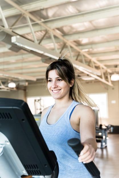 Garota fitness usando instrutor elíptico Foto gratuita