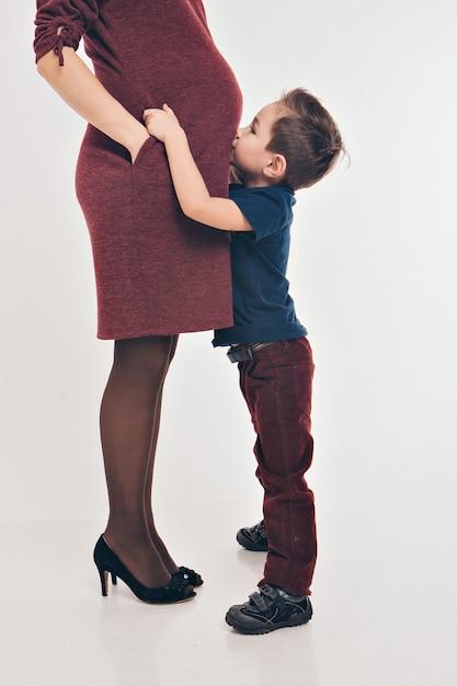 Garota garoto feliz abraçando a barriga da mãe grávida, gravidez e novo conceito de vida Foto Premium