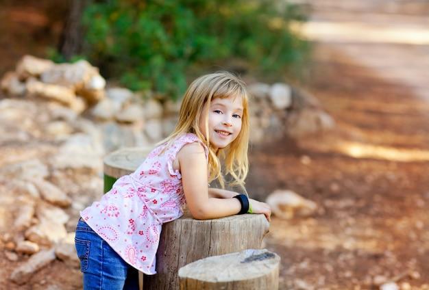 Garota garoto loiro na floresta de tronco de árvore Foto Premium