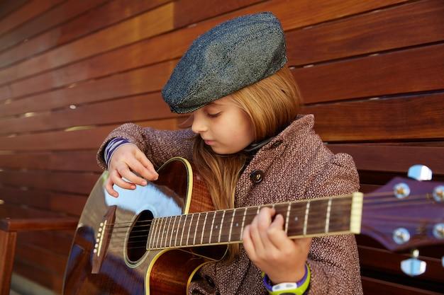 Garota garoto loiro tocando guitarra com boina de inverno Foto Premium