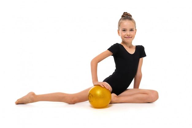 Garota ginasta em preto completo altura total fica em uma meia página com uma bola amarela Foto Premium