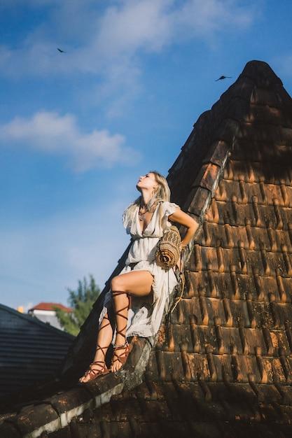 Garota hippie com longos cabelos loiros em um vestido no telhado. Foto gratuita