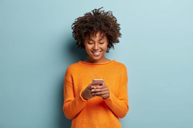 Garota hipster satisfeita com corte de cabelo afro, digita mensagem de texto no celular, gosta de comunicação online Foto gratuita