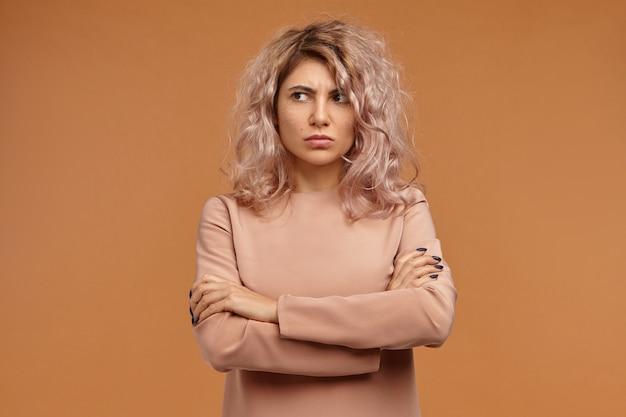 Garota hipster teimosa e rabugenta com cabelos volumosos expressando desrespeito e indiferença, sem falar com você, desviando o olhar com uma expressão facial descontente Foto gratuita
