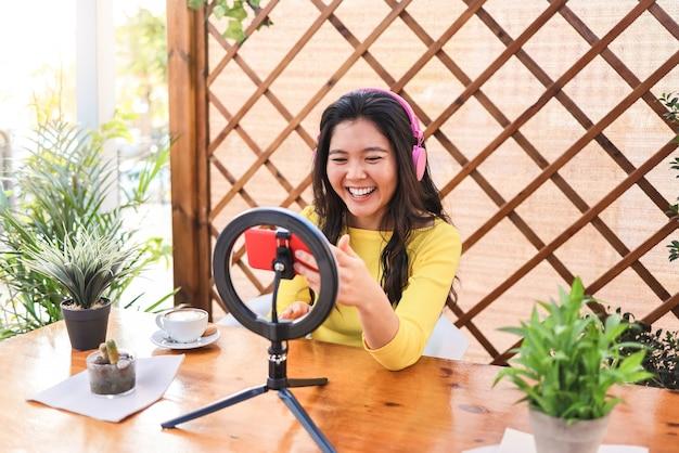 Garota influenciadora asiática transmitindo online com câmera de smartphone ao ar livre em restaurante Foto Premium