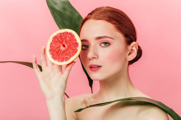 Garota inspirada posando com folhas verdes e cítricos. foto de estúdio de mulher gengibre com pé de toranja sobre fundo rosa. Foto gratuita