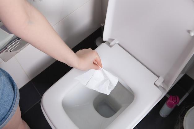 Garota jogando papel no banheiro Foto Premium