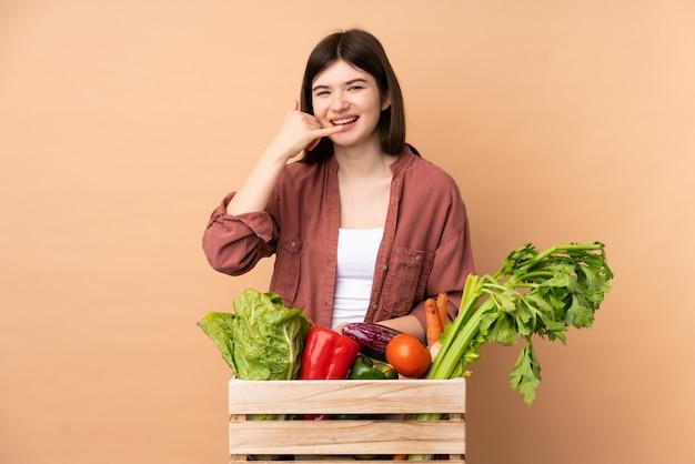 Garota jovem agricultor com legumes recém colhidos em uma caixa fazendo gesto de telefone Foto Premium