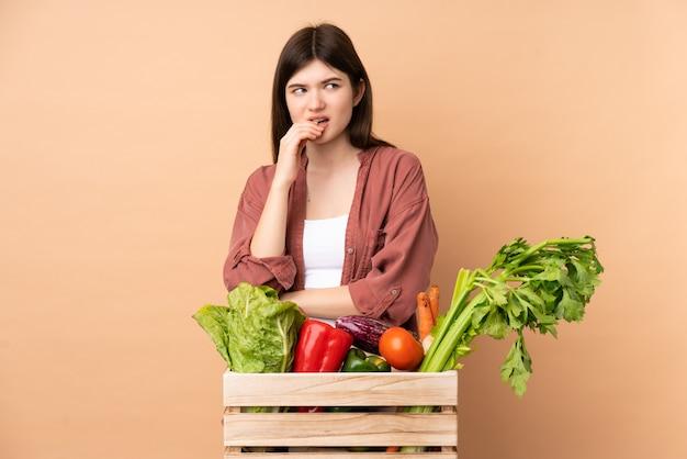 Garota jovem agricultor com legumes recém colhidos em uma caixa nervosa e assustada Foto Premium