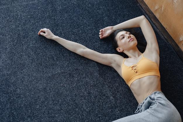 Garota jovem atraente aptidão deitado no chão perto da janela, descansando nas aulas de ioga Foto gratuita