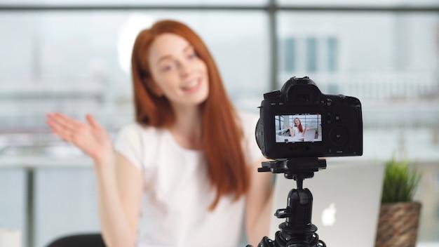 Garota jovem bonita blogueiro trabalhando no escritório enquanto fotografava na câmera Foto Premium
