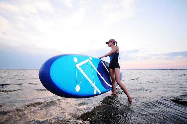 Garota jovem e atraente com placa sup no fundo do mar e pôr do sol Foto Premium