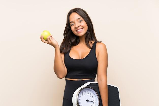 Garota jovem esporte com máquina de pesagem sobre fundo isolado Foto Premium