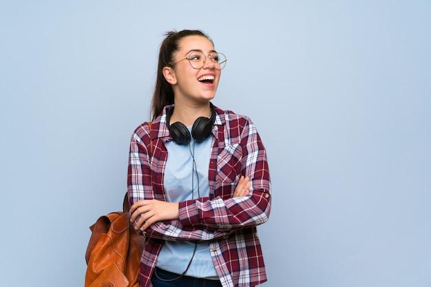 Garota jovem estudante sobre fundo azul Foto Premium