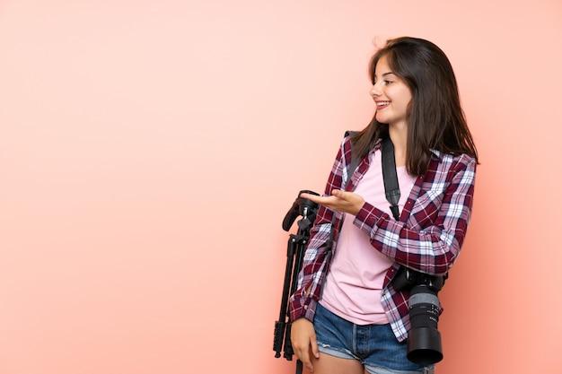 Garota jovem fotógrafo sobre parede rosa isolada, estendendo as mãos para o lado para convidar para vir Foto Premium