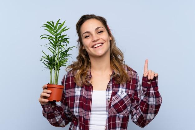 Garota jovem jardineiro loira segurando uma planta apontando para cima uma ótima idéia Foto Premium
