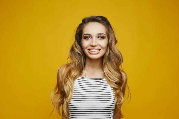 Garota jovem loira com um sorriso encantador vestido branco listrado Foto Premium