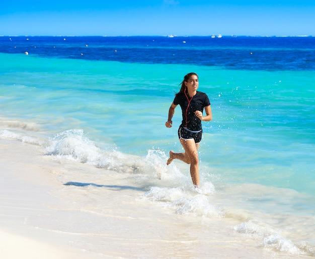 Garota latina correndo na praia do caribe Foto Premium