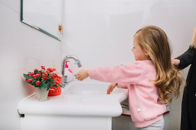 Garota lavando a mão na pia do banheiro Foto gratuita