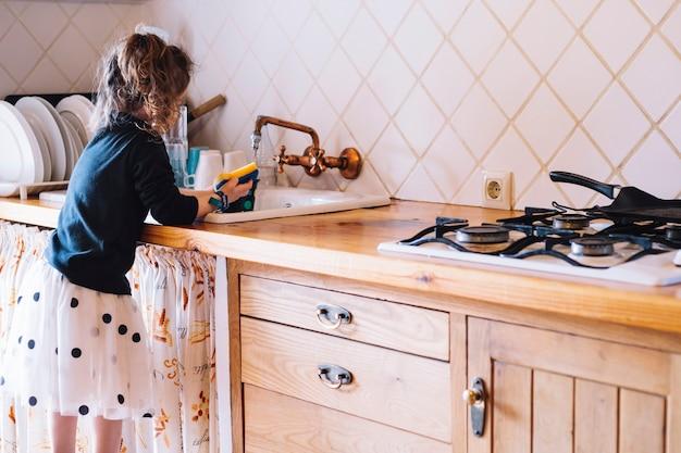 Garota lavando o copo na pia da cozinha Foto gratuita