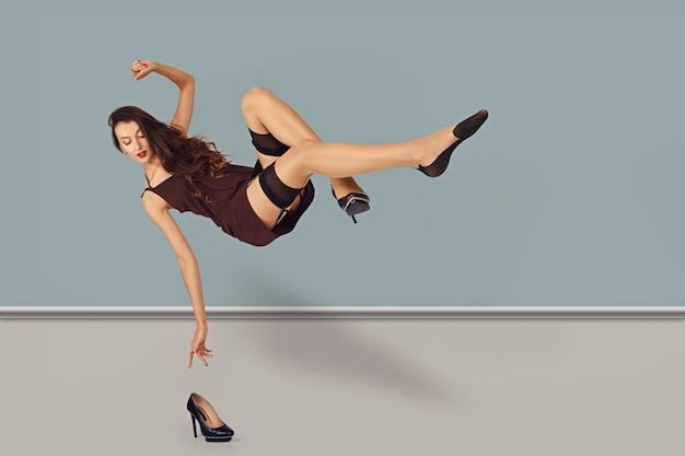 Garota levitando em vestido curto e meias atingindo a mão para um sapato no chão Foto Premium
