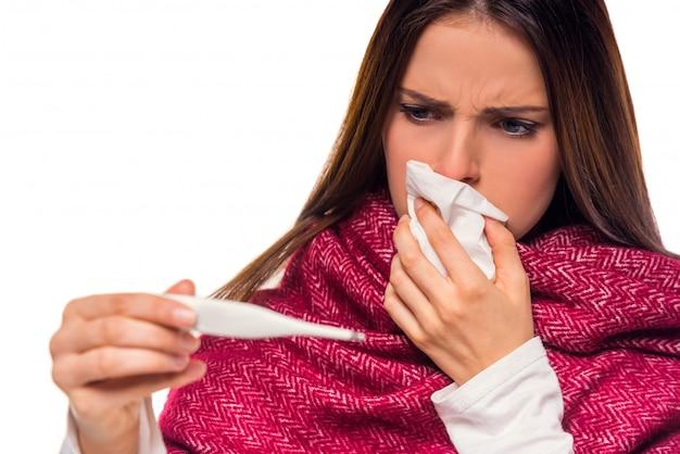 Garota limpa o nariz e olha para o termômetro. Foto Premium