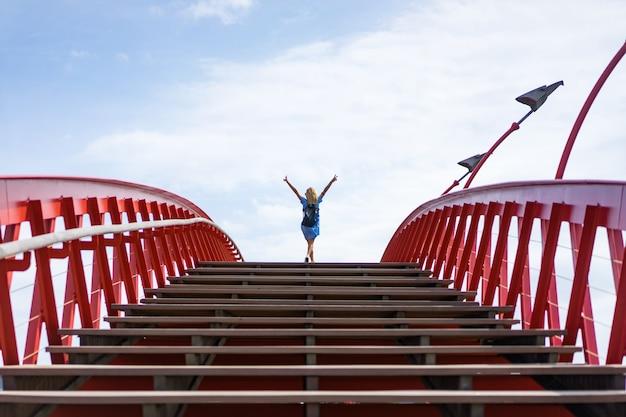 Garota linda em um vestido azul posando na ponte Foto gratuita