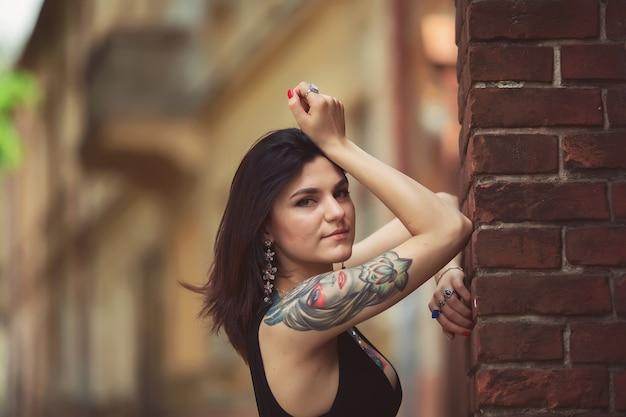 Garota linda em um vestido preto fica perto de estruturas arquitetônicas, posando Foto Premium