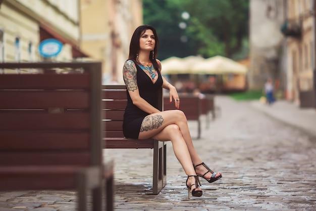 Garota linda em um vestido preto, sentado em um banco, coberto de tatuagens Foto Premium
