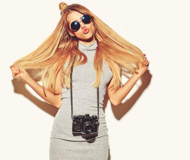 Garota linda mulher loira bonita feliz em roupas de verão casual hipster tira fotos segurando a câmera fotográfica retrô isolada em um branco com cabelos nas mãos Foto gratuita
