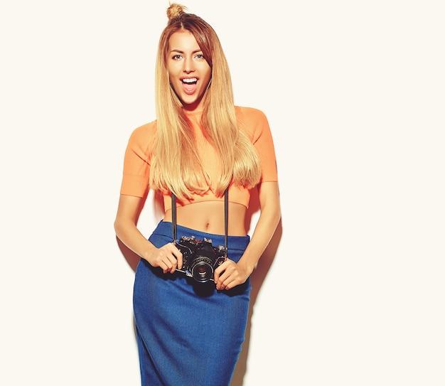 Garota linda mulher loira bonita feliz em roupas de verão casual hipster tira fotos segurando a câmera fotográfica retrô isolada no branco Foto gratuita