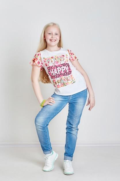 Garota loira adolescente em jeans e uma t-shirt Foto Premium