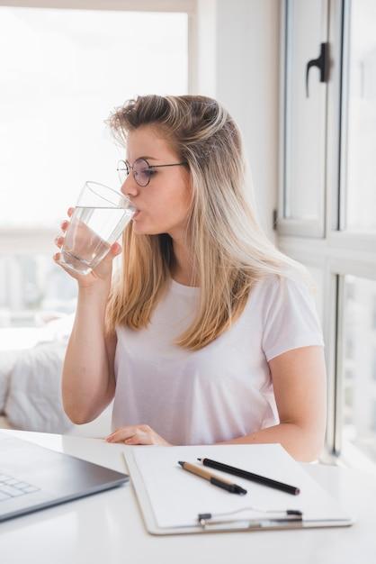 Garota loira bebendo água no trabalho Foto gratuita