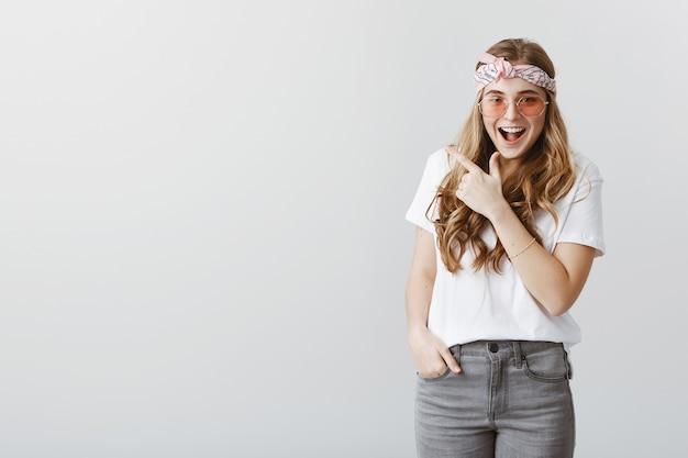 Garota loira bonita e feliz apontando os dedos no canto superior esquerdo com uma cara animada Foto gratuita