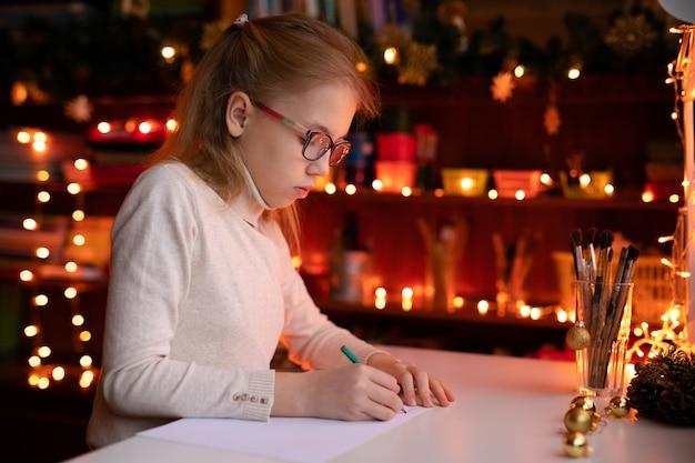 Garota loira criança com grande rosa ans óculos escuros escrevendo carta para o papai noel Foto Premium