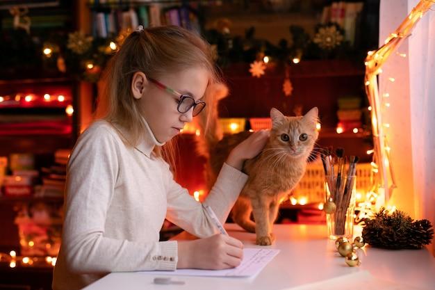 Garota loira criança com grandes óculos cor de rosa e pretos, escrevendo a carta para o papai noel Foto Premium