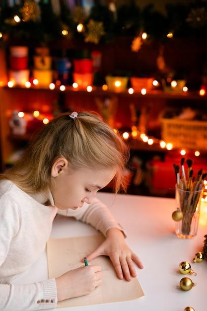 Garota loira criança escrevendo a carta para o papai noel ou algo de desenho na com bokeh amarelo quente Foto Premium
